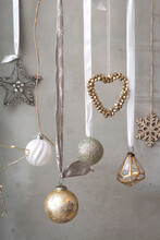 Christmas Decorations, Close Up Of Silver, White And Golden Christmas Baubles On Ribbons