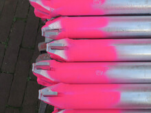 Ends Of The Metal Pipes Of Scaffolds Painted Pink Laying On The Street