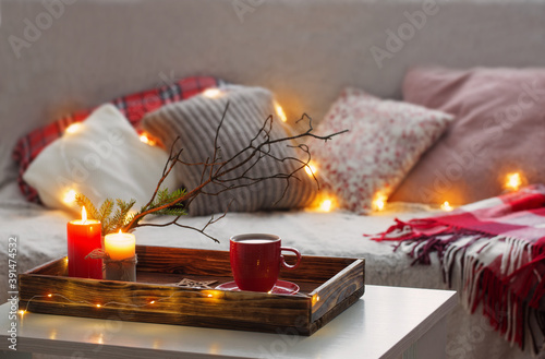 Papel de parede Red cup of tea on tray with burning candles on background sofa with pillows