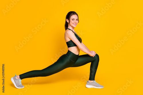 Fotografering Photo of sportive young lady fitness stretching sit one leg wear sports suit top