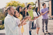 Leinwandbild Motiv Photo of company of friends standing smile enjoy arms clap applaud weekend meeting restaurant outside
