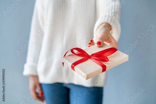 Fotografiet Close up cropped shot of woman hands with red polished nails holding gift box wi
