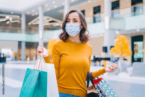 Fototapeta Portrait of casually dressed confident young woman wearing protecting medical mask while walking in mall with bunch of shopping bags in hands obraz