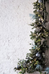 Christmas decoration of branches and garlands on the background of an old brick wall