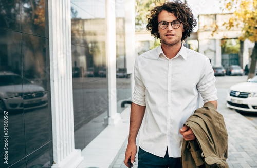 Obraz Handsome businessman in eyewear smiling broadly posing outdoors. Male entrepreneur resting in the city street. Smart guy in casual wears spectacles with curly hair walking outside after work - fototapety do salonu