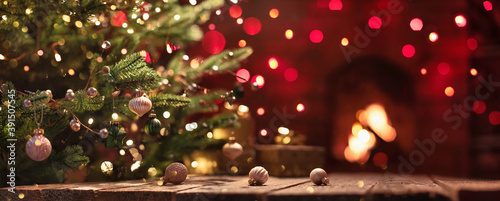 Fotografiet Christmas Tree With Decorations Near A Fireplace