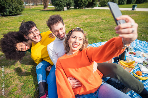 Group of four multiethnic diverse friends outdoor using smartphone taking selfie Fototapet