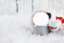 Empty Snow Globe With Copy Space Surrounded By Santa Hat With Falling Snow. Shallow Depth Of Field With Selective Focus On Snowglobe And Free Space For Text Available.