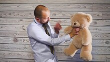 Young Angry Businessman Beating A Stuffed Bear Toy In His Office. Concert On The Theme Of Frustration
