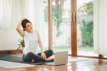 Smiling Asian Woman Doing Yoga Neck Stretching Online Class From Laptop At Home In Living Room. Self Isolation And Workout At Home During COVID-19.