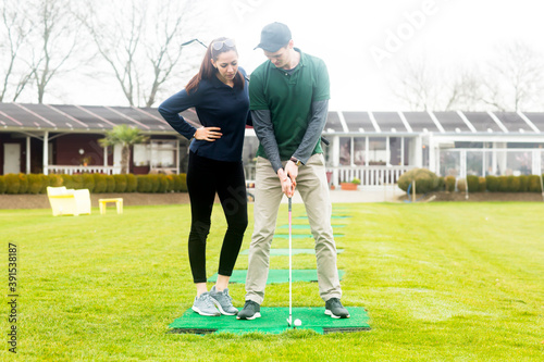 young couple playing golf together