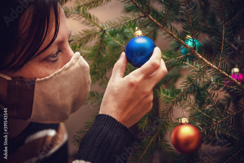 Papel de parede Woman wearing a face mask and is decoration a christmas tree with baubles or bal