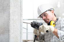 Man Using An Electric Pneumatic Drill Making A Hole In Wall, Professional Construction Worker With Safety Hard Hat, Hearing Protection Headphones, Gloves And Protective Glasses.