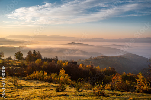 dawn green glade on a background of mountains in the fog the sky shimmers with beautiful colors. Autumn season. #391555539