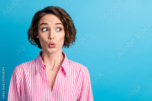 Photo of wavy guilty cute woman dressed pink striped shirt made lips pouted look empty space isolated blue color background