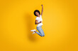 Full length body size photo of cheerful happy girl with black skin jumping high keeping hand up laughing isolated on bright yellow color background