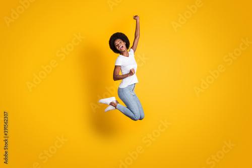 Full length body size photo of cheerful happy girl with black skin jumping high Fotobehang