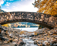 Stone Arched Bridge Over A Mountain River In The Colorful Autumn Forest.