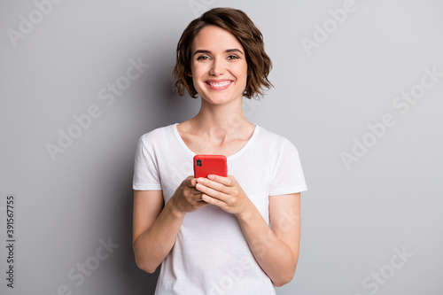 Obraz Photo of young attractive girl happy smile hold cellphone mobile chat type isolated over grey color background - fototapety do salonu