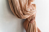 A beautiful blonde curly leggy big breasted naked girl sensually poses at the wall, covering nudity of her excellent body with a large piece of beige cloth. Close up photo. Artistic design