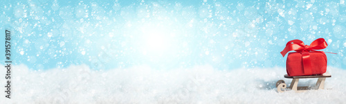Fotografija Banner with sleigh delivering Christmas or New Year red present box on blue snow
