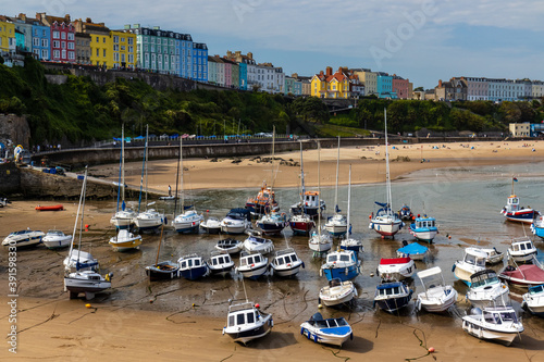 Boats resting on the sand at lowtide in the picturesque harbour and seaside town Wallpaper Mural