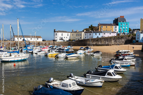 Photo Boats resting on the sand at lowtide in the picturesque harbour and seaside town