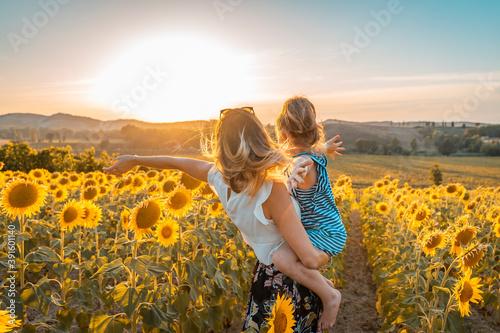Fotografija giovane mamma in braccio la figlia in campo di girasoli guardano il futuro