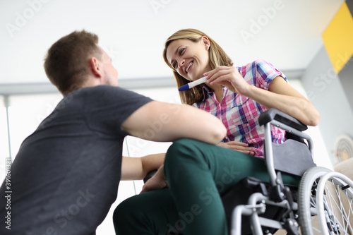 Woman in wheelchair happily smiles at man and holds pregnancy test Canvas Print