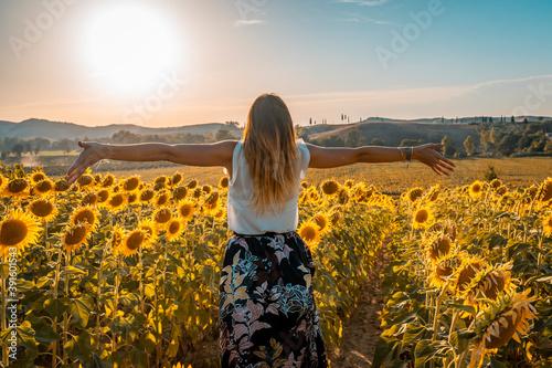 Fotografija Donna bionda abbraccia il sole in un campo di girasoli in toscana