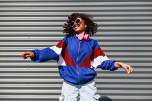 Cool Black Girl With Curly Hair, Glasses, 90s, 80s, Retro Hip Hop Style, Dancing Against A Metal Wall, Dynamics And Expression