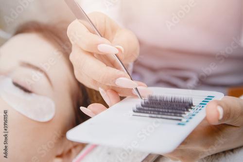 Slika na platnu Eyelash extension procedure. Woman master making fake long lash