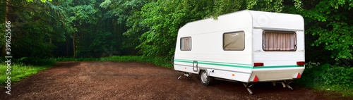 Fototapeta Caravan trailer with a bicycle parked on the rural road in a green forest