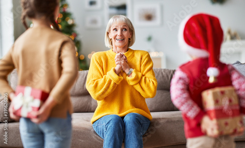 happy family grandchildren gives a cheerful smiling grandmother a Christmas gift Canvas Print