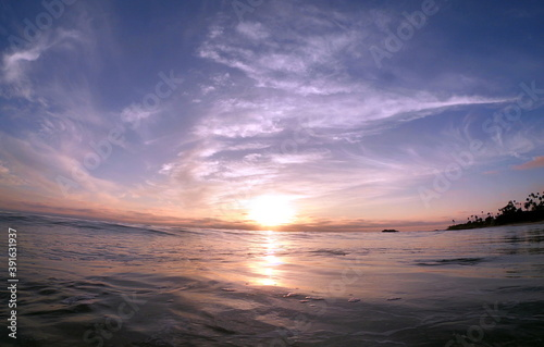 Vibrant sunset reflected by the oily smooth ocean surface POV IN WATER
