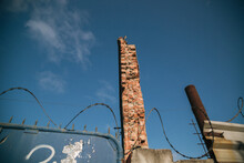 Low Angle Shot Of A Tall Destroyed Building With Barbed Wires