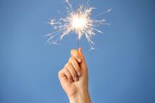 Woman Holding Bright Burning Sparkler On Light Blue Background, Closeup