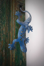 Vertical Shot Of A Blue Metal Lizard Decoration