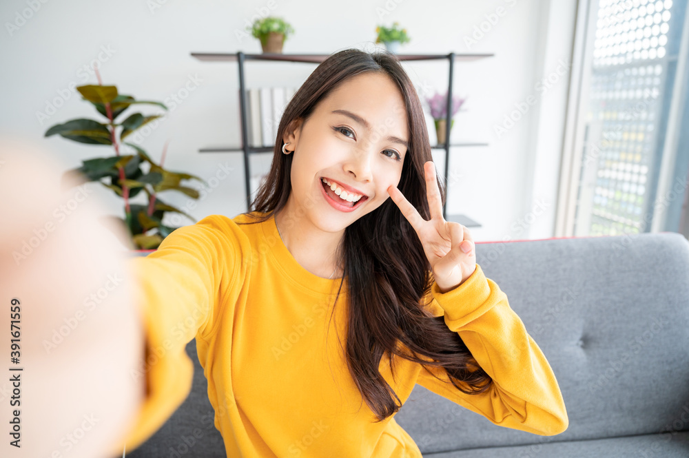 Fototapeta Pretty young asian female with big smile sitting at living room. She having fun taking light cheerful selfie on blurred background