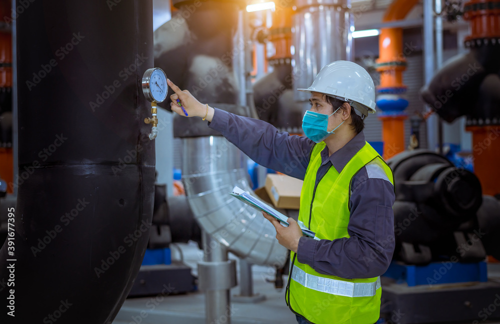 Fototapeta Engineer under checking the industry cooling tower air conditioner is water cooling tower air chiller HVAC of large industrial building to control air system ,wearing mask for protect pollution.