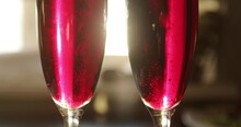 Rising Up Bubbles In Red Sparkling Wine. Two Glasses Of Pink Champagne In The Sun Glare.