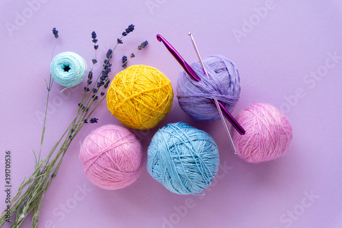 Fotografering Flat lay of colored yarn balls for crocheting with lavender on a lilac backgroun