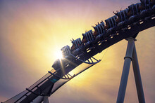 Funny People Riding Roller Coaster With Sun Light