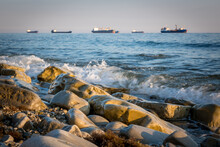 Stone Seashore, Waves And Cargo Ships Waiting In Line To Enter The Port At The Background