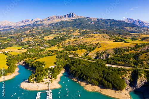 Scenic mountain landscape of French Alps with turquoise waterspace of artificial Lake Serre-Poncon in sunny summer day, France