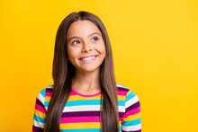 Photo Of Creative Little Girl Look Up Empty Space Toothy Smile Wear Striped Shirt Isolated Yellow Color Background
