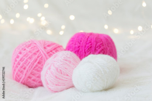 Fotografering Pink knitting balls lie against a yellow bokeh background.