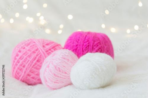 Tela Pink knitting balls lie against a yellow bokeh background.