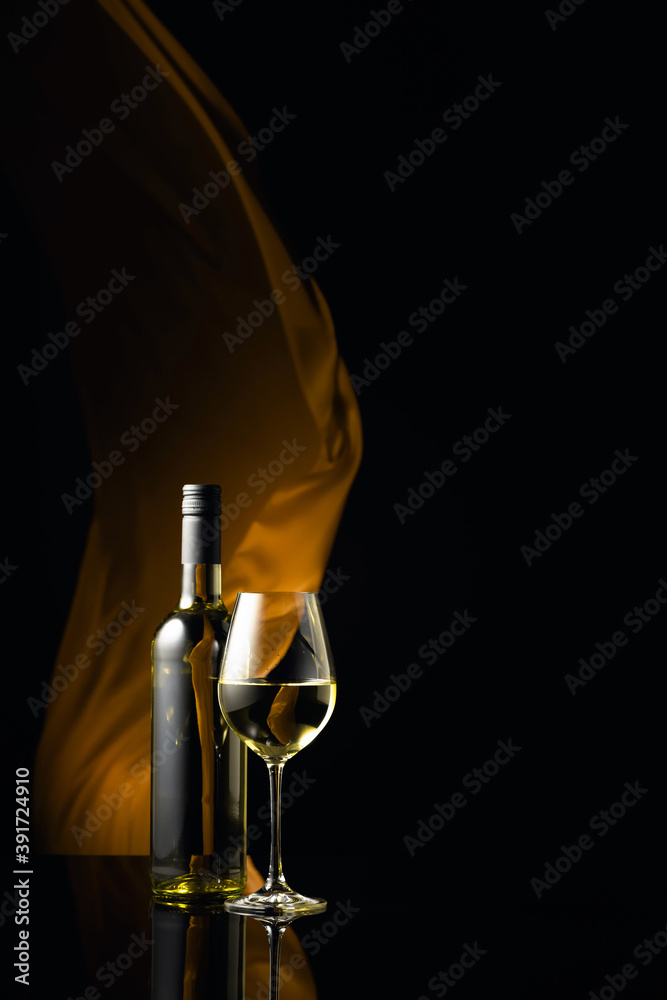 Fototapeta Вottle and glass of white wine on a black reflective background.