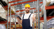Leinwandbild Motiv profession, logistics and job concept - happy smiling male worker or loader in yellow helmet and overall with tablet pc computer showing thumbs up over warehouse background